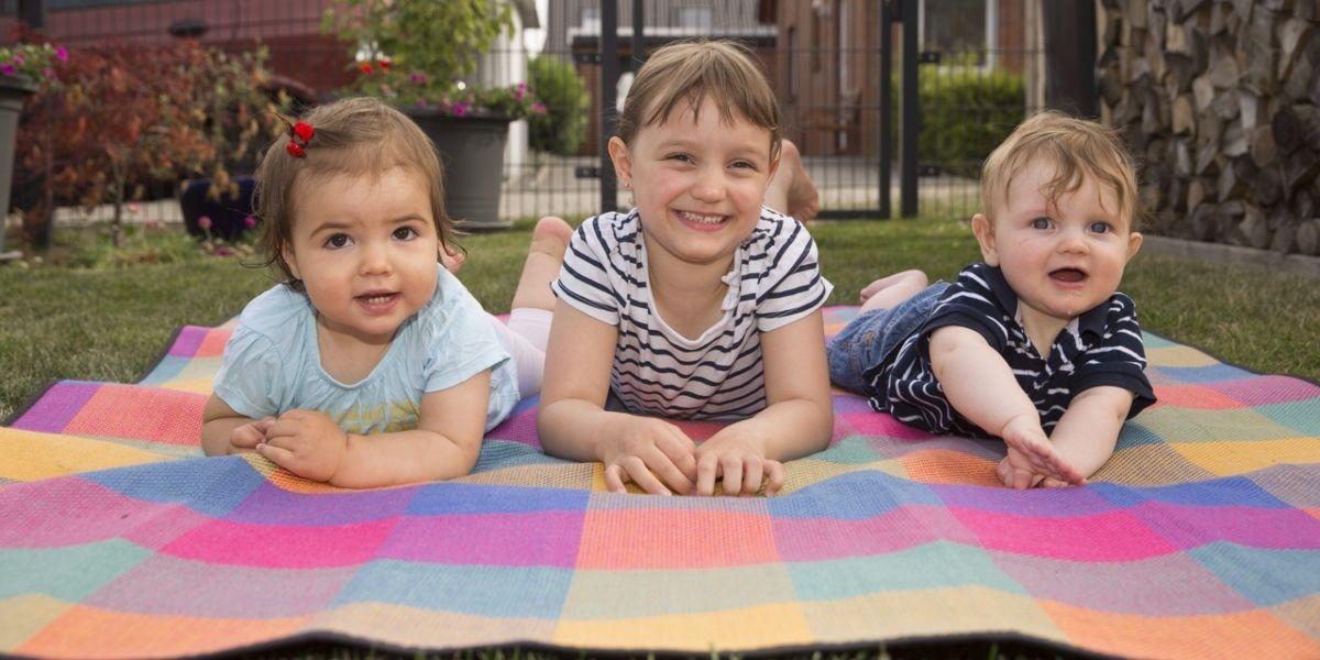 Drei Kinder liegen auf einer Picknickdecke