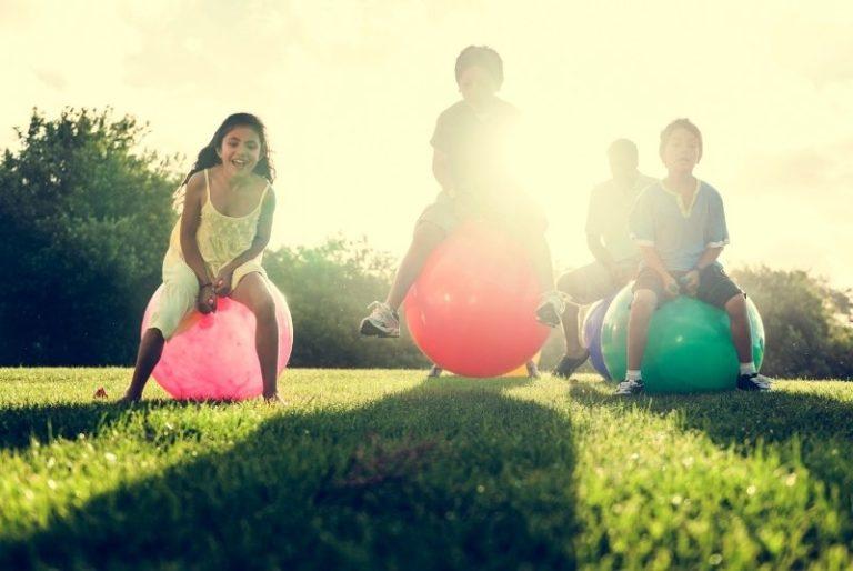Kinder auf Hüpfpferden im Sonnenschein