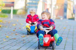 Kinder fahren auf einem Rutschauto